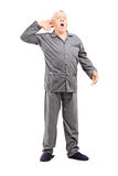 Sömnig pensionär, i pyjamassträckning Royaltyfri Foto