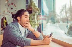 Sömnig rolig man, hand på mun som gäspar se den smarta telefonen som borras av telefonkonversation som smsar royaltyfria foton