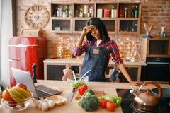Sömnig svart kvinna i förkläde som lagar mat på köket royaltyfri foto