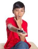 Sömnig ung asiatisk flicka med TVfjärrkontrollen royaltyfri foto