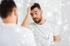 Sömnig ung man framme av spegeln på badrummet Royaltyfri Bild
