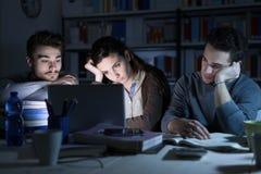 Sömniga tonåringar som sent studerar på natten Arkivbild