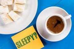 Sömnigt textbegrepp med koppen kaffe på tabellen arkivfoto