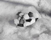 Sönderriven boll för att spela fotboll som ligger på snön royaltyfri foto