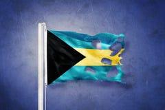 Sönderriven flagga av det Bahamas flyget mot grungebakgrund Fotografering för Bildbyråer