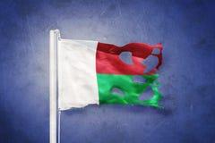 Sönderriven flagga av det Madagascar flyget mot grungebakgrund vektor illustrationer