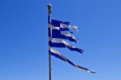 Sönderriven grekisk flagga mot blå himmel Royaltyfria Bilder