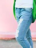 Sönderriven jeans på en rosa bakgrund på flickas bild för benljus Arkivbilder
