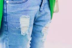 Sönderriven jeans på en rosa bakgrund så nära främre fokus Royaltyfria Bilder