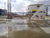 Sönderriven slang av brandslangen Vatten fylld konkret trottoar Olje- behållare och rörledningar Utrustningoljefält av västra Sib Fotografering för Bildbyråer