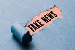 Sönderrivet papper som avslöjer uttrycks`en, fejkar nyheterna`, royaltyfri bild
