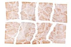Sönderrivna ark av brunt åldrigt papper på det vita bakgrundsslutet upp, trasiga strimlor av den gamla pappers- designen, kopieri fotografering för bildbyråer