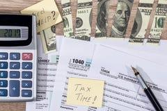 Sönderrivna dollar på den skattform, penna och räknemaskinen royaltyfri fotografi