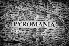 Sönderrivna stycken av papper med ordpyromaniaen royaltyfria bilder