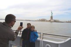 Söner som fotograferas på statyn av Liberty Tom Wurl Royaltyfria Foton