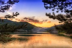 Sörja trädfilialer som inramar den reflekterande sjön och dramatisk himmel för guld- timme med mörker, fluffiga moln Royaltyfria Bilder