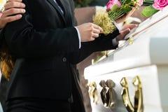 Sörjande folk på begravningen med kistan Royaltyfri Foto