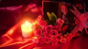 Söt ögonblicksvalentindag med blommabuketten och stearinljusbränning