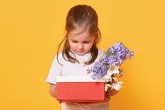Söt barnflicka som rymmer den röda asken med gåva och buketten av blommor, litet barnbekymmer, medan förbereda sig att gratulera  royaltyfri bild
