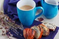 Söt bulle med vallmofrön med en kopp kaffe eller en cappuccino Arkivbild