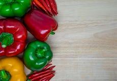 Söt chili och paprika på en träbakgrund Royaltyfri Bild