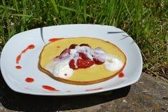 Söt efterrätt - pannkakor med jordgubbar och kräm på den vita plattan Arkivfoton