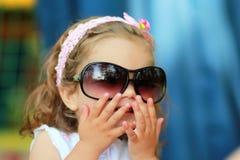 Söt en årig flicka som för mamma` s för ` s stulen solglasögon och lyckligt att bära dem som försöker att se som ett fullvuxet up Royaltyfri Fotografi