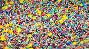 Söt färgrik konfektbestänkandetextur med gula prickar för stjärnasockerstänk Royaltyfri Bild