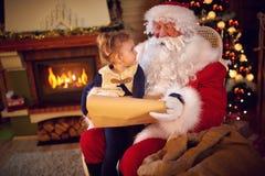 Söt flicka och Santa Claus som väljer hennes gåva från lista Royaltyfria Bilder