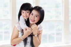 Söt flicka som kramar hennes moder Fotografering för Bildbyråer