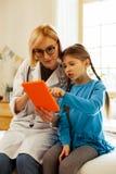 Söt flicka som pekar på minnestavlan medan doktor som ser den royaltyfri foto