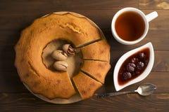 Söt frodig muffin med jordgubbedriftstopp och te Arkivbild