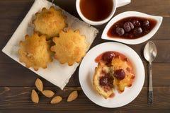 Söt frodig muffin med jordgubbedriftstopp och te Royaltyfri Bild
