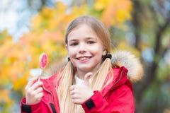 Söt godis för trick eller för fest Lag för ungeflickakläder för nedgångsäsong Det gladlynta barnet äter solig dag för klubbagodis royaltyfria bilder
