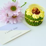 Söt grön kaka på en vit bakgrund royaltyfria foton