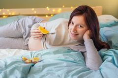 Söt gravid caucasian kvinna som ligger på säng med apelsinen Arkivbilder