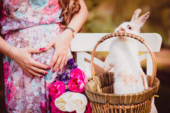 Söt härlig gravid kvinna med blommor och påskkaninen Arkivbild