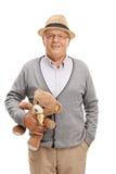 Söt hög gentleman som rymmer en nallebjörn Arkivbild