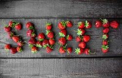 söt jordgubbe Inskrift från bär på träbakgrund Royaltyfri Fotografi