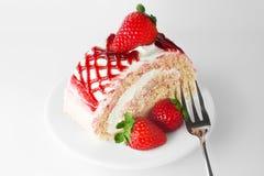 Söt jordgubbekaka på den vita plattan med gaffeln arkivfoton