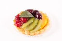 Söt kaka med frukter som isoleras på vit royaltyfria bilder