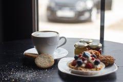 Söt kaka med kopp te som isoleras på vit Royaltyfria Bilder
