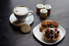 Söt kaka med kopp te som isoleras på vit Fotografering för Bildbyråer