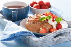 Söt kanelbrun rulle med kräm och jordgubben för frukost Arkivfoton