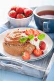 Söt kanelbrun rulle med kräm och jordgubben för frukost Royaltyfri Foto