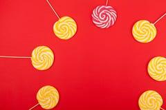 Söt karamellgodis på en röd bakgrund Ljusa klubbor fotografering för bildbyråer