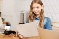 Söt le tonårs- flicka som rymmer en meny fotografering för bildbyråer