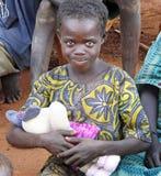Söt liten afrikansk flicka som är extatisk med den första mjuka leksaken arkivfoton