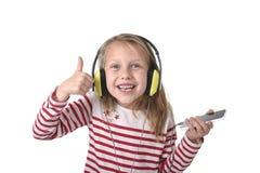 Söt liten flicka med blont hår som lyssnar till musik med hörlurar och mobiltelefonen som sjunger och dansar som är lycklig arkivfoton