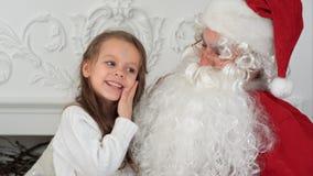 Söt liten flicka på den Santa Claus varven som berättar honom vad hon önskar för jul arkivbild